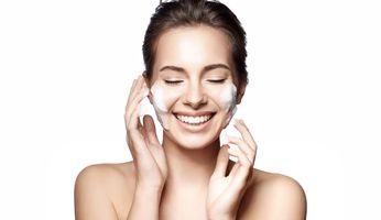 Frau wäscht sich das Gesicht mit Reinigungsschaum
